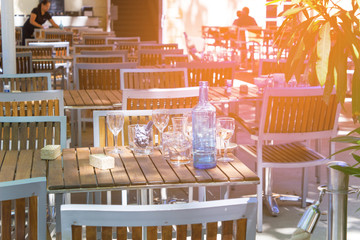 Soft focus,  A glass of water, a bottle of water and a glass of wine after a drink are placed on a wooden table with the sun in the evening.