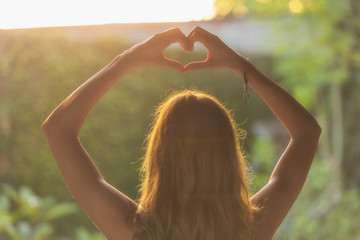 Girl holding a heart-shape with hands outdoors.