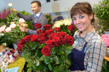 female florist holding bouquet of roses