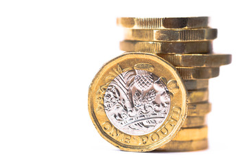 Stack of British Pound coins with one coin stood up at front