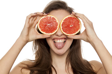 Young sexy woman posing with slices of red grapefruit on her face on white background