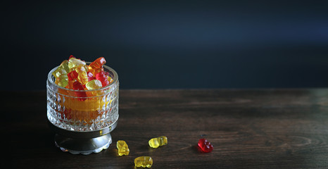 Marmalade in a vase on the table. Sweets in a bowl on a black ba