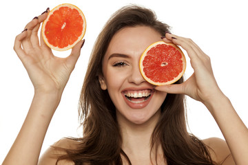 Happy young woman posing with slices of red grapefruit on her face on white background