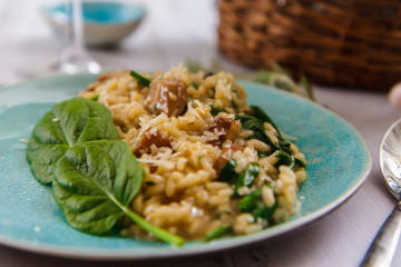 Risotto with mushrooms and spinach on a ceramic plate