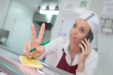 Worker taking telephone order, making hand gesture for quantity