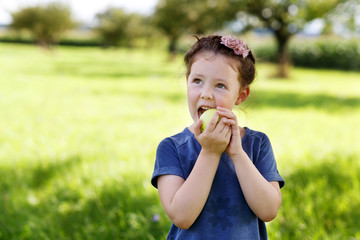 Adorable little preschool kid girl eating green apple on organic farm