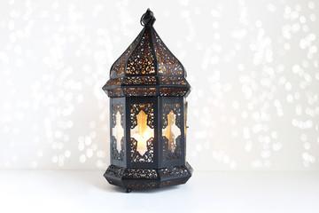 Ornamental dark Moroccan, Arabic lantern on the white table. Burning candle, glittering bokeh lights. Greeting card for Muslim community holy month Ramadan Kareem. Festive background.