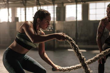 Foto auf AluDibond Fitness Woman doing battle rope workout at gym