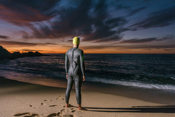 Rear view of triathlete standing at beach during sunset