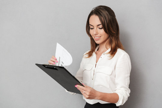 Amazing cheerful young business woman holding clipboard.