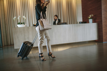 Business woman arriving at hotel hallway with baggage