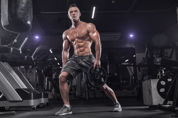 Handsome man doing exercises in the gym on a dark background, using dumbbells, doing sports exercises for the development of the muscles of the back, biceps, triceps.