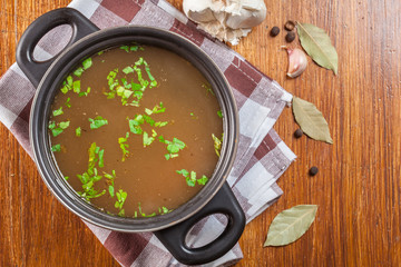 Tasty meat broth in a dark cooking dish