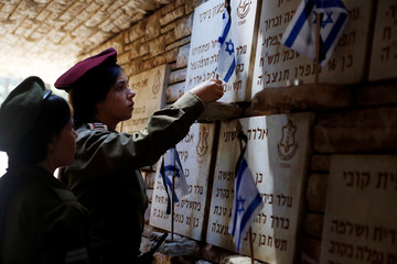 Israeli soldiers place flags next to the names of soldiers killed in fighting during the 1948 war of IsraelÕs founding, at the Mount Herzl military cemetery ahead of Memorial Day, in Jerusalem