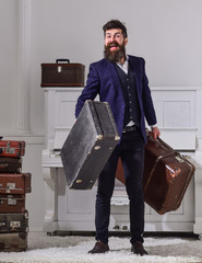 Man, traveller with beard and mustache with luggage, luxury white interior background. Macho elegant on smiling face stands near pile of vintage suitcase, holds suitcases. Baggage delivery concept.