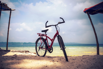 Red bicycle parked in the beach. Bicycle parking in the beach sand.