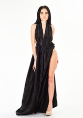 Lady, sexy girl in dress. Fashion dress concept. Woman in elegant black long evening dress with decollete, white background. Attractive girl wears expensive fashionable evening dress with erotic slit.