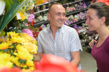 young florist is helping male customer to choose a bouquet