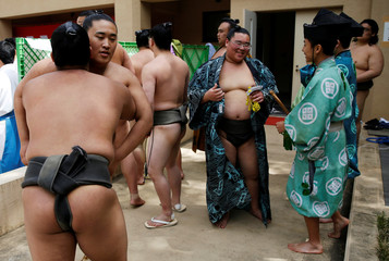 Sumo wrestlers and referees wait for the start of an annual sumo tournament dedicated to the Yasukuni Shrine in Tokyo