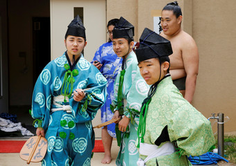 Young sumo referees wait for the start of an annual sumo tournament dedicated to the Yasukuni Shrine in Tokyo