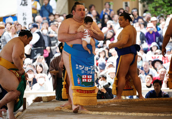 Georgian sumo wrestler Gagamaru carries a baby in a sumo ring during an annual sumo tournament dedicated to the Yasukuni Shrine in Tokyo