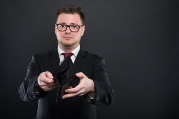 Portrait of business man showing empty wallet.