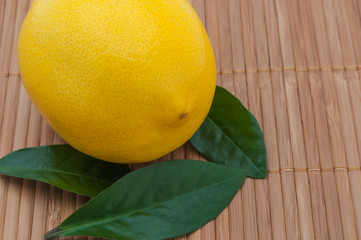 large yellow lemon with green leaves close-up on bamboo mat.