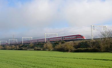 high speed italian train runs through the green Tuscan countryside