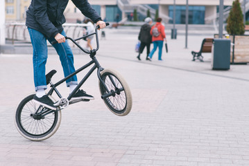 BMX freestyle. Young man doing tricks in a park on a BMX bike. The cyclist trains on the back wheel of the bike