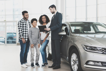 African american family at car dealership. Salesman is signing papers for new car.