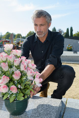 putting flowers on a grave