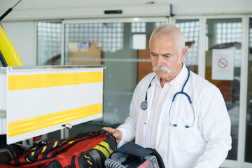 senior doctor next to an ambulance
