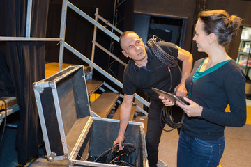 Man and woman packing away sound equipment
