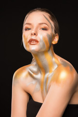 Beauty portrait of seductive blonde model with gold and silver paint on her shoulders and face