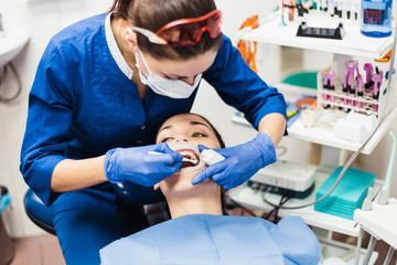 Dentist holding tooth whitening procedure