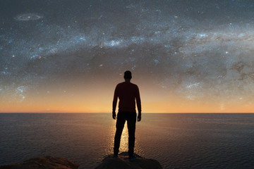 A man looks at the stars.  Elements of this image furnished by NASA.