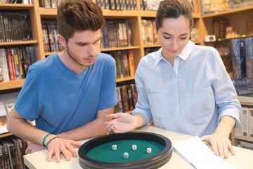 teenage girl and boy playing dice