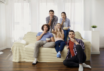 A group of friends watching TV sitting on the couch in the room.
