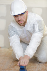 young man sanding floor