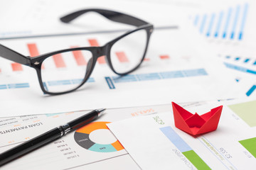 Boats made of paper graph on notebook with glasses and pen.Business Analysis concept.