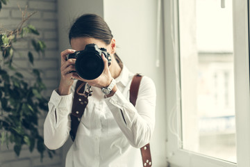 Pretty woman is a professional photographer with dslr camera