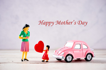 Miniature people: A mother who is given a heart in love by little child girl   with little bettle pink car, the concept of Mother's Day, blank background   for text, macro shot