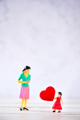 Miniature people: A mother who is given a heart in love by little child   girl, the concept of Mother's Day, blank background for text, macro shot