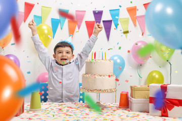 Overjoyed kid with a party hat and birthday cake