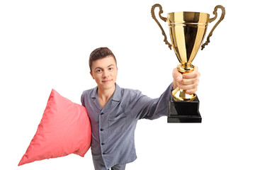Teenage boy in pajamas holding a pillow and a golden trophy