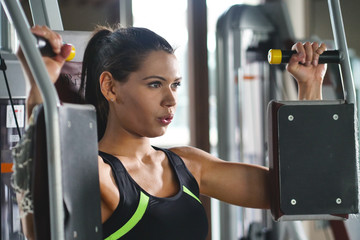 Beautigul fit woman (girl) trains in the gym. Concept: Sport, passion, fitness, love.