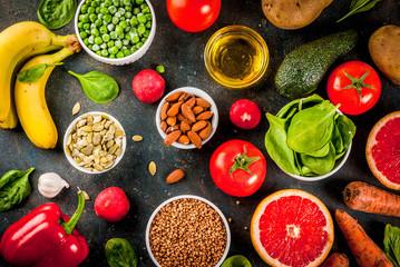 Healthy food background, trendy Alkaline diet products - fruits, vegetables, cereals, nuts. oils, dark blue concrete background above