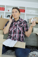 worried confused woman on the phone assembling furniture