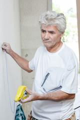 Builder taking measurement of wall