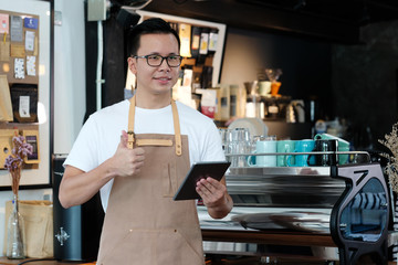 Young asian man, barista, using tablet at cafe counter background, food and drink concept